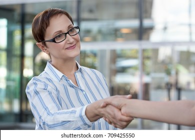 Business woman shaking hands in the office. Business meeting. Customer service. Hospitality concept.