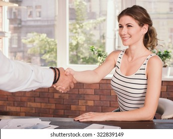 Business woman shaking hands while sitting at the table in home office