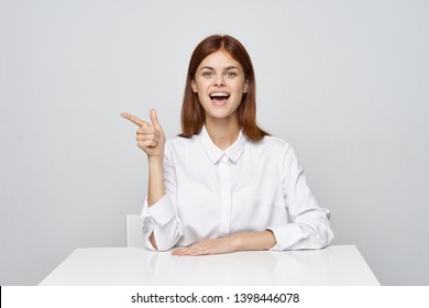 Business woman in shirt is sitting at the table emotions office work