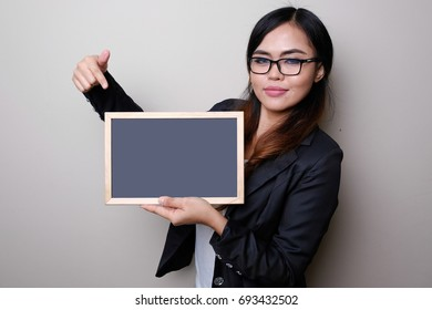 Business woman show something on blank black board