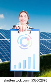 Business woman showing clipboard with charts about profit of regenerable power usage