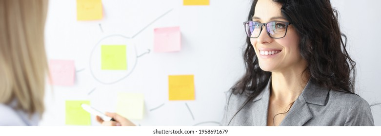 Business woman showing colleague with ballpoint pen stickers on chalkboard
