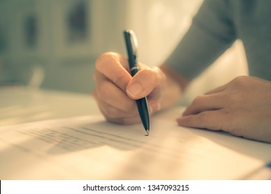 Business woman signing his resignation letter on his desk before sending to his boss to quit a job. Resignation letter information