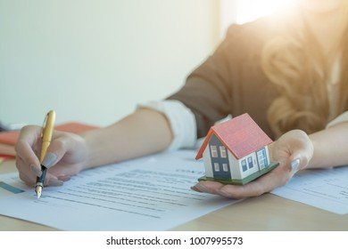 Business woman signs contract and holding hoouse architectural model, Real estate concept