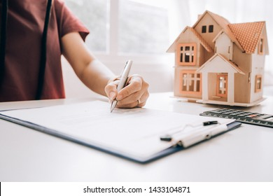 Business woman signs contract with hoouse architectural model, Real estate concept