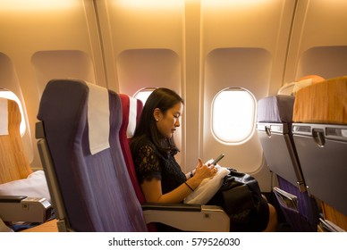 Business woman sit inside airplane and working on cell phone