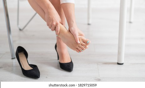 A business woman sits in an office on a chair, takes off her high-heeled shoes and massages her tired feet