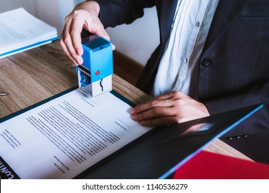 Business woman sitting with brass scale at lawyer desk, Lawyer working hand holding automatic stamp important documents in office. lawyer and law ,judiciary and legislature courtroom legal concept.
