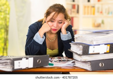 Business woman sitting by desk, paper files spread out, leaning head on hands looking overwhelmed and tired