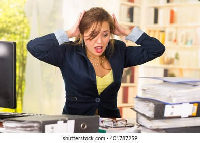 Business woman sitting by desk, paper files spread out, shocked and frustrated body language