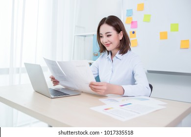 Business woman sitting by the table and working with laptop