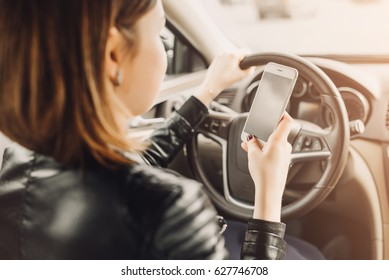 Business woman sitting in car and using her smartphone. Mockup image with female driver and phone screen