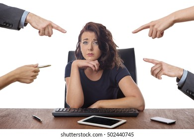 business woman sitting at desk surrounded by pointing fingers