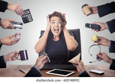 business woman sitting at desk surrounded by many hands holding objects