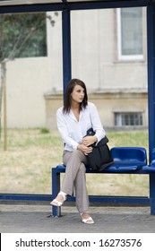 business woman sitting down at the bus stop waiting