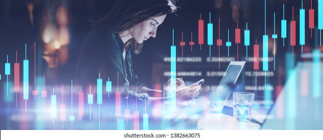 Business woman sitting at night office in front laptop computer and using her mobile phone. Red and green candlestick chart and stock trading computer screen background. Double exposure. Wide