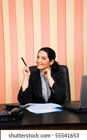 Business woman  sitting on chair at desktop in an office and indicate with pencil to copy space
