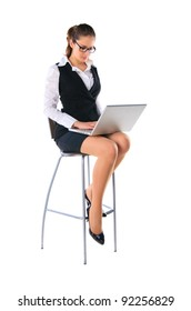 Business woman sitting on a high chair and works on the laptop. Isolated on white.