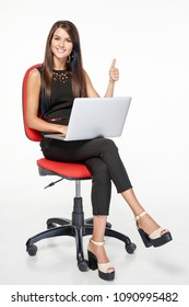 Business woman sitting on office chair working with laptop looking at camera smiling gesturing thumb up, full length portrait