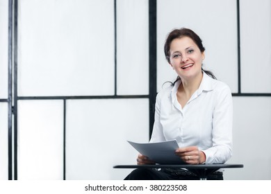 business woman sitting on table with papers in hands