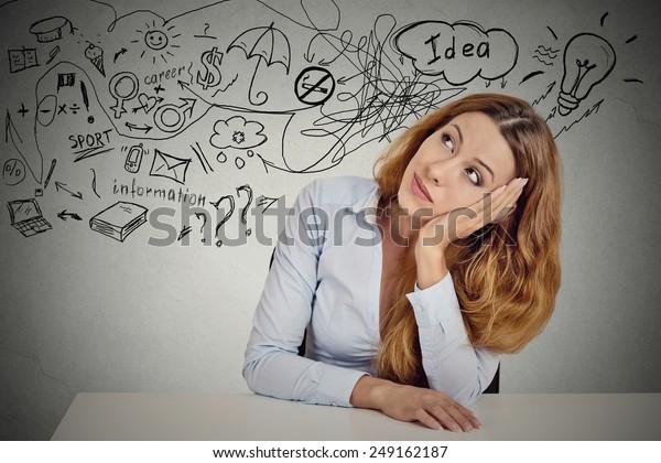 Una mujer de negocios sentada a la mesa tiene muchas ideas para hacer planes de futuro aislado en el fondo gris de la pared de la oficina. Percepción de carrera. Concepto de equilibrio de la vida personal. Proceso de toma de decisiones