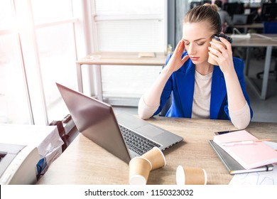 Business woman is sitting at the table and keeping her hands close to the head. She has a headache. She stopped working on laptop. Woman did a pause.