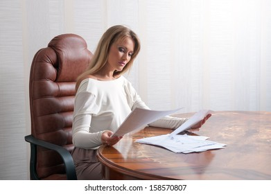 Business woman sitting at a table and reads