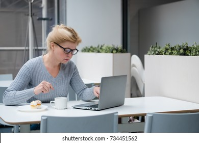 Business woman sitting at table and using laptop. On table is laptop and cup of coffee.