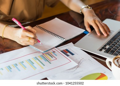 Business woman sitting at the work table with instrument plan and laptop