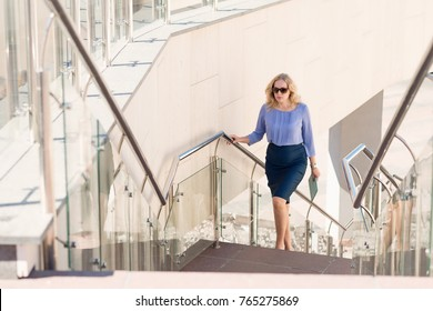 Business woman in a skirt and sunglasses climbs the stairs
