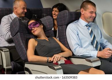 Business woman sleep during night flight airplane cabin passengers