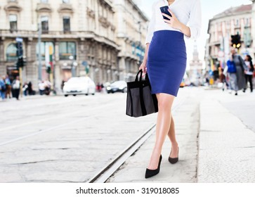 A business woman with smart phone walking in the street. Beautiful legs with office fashion. bag and shoes in the city.