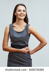Business woman smiling with teeth posing on light gray background. Business style gray dress.