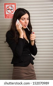 Business woman smokes against signs prohibiting smoking