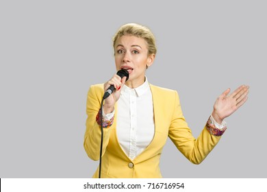 Business woman speaking and gesticulating. Young business lady speaking on conference standing on grey background.
