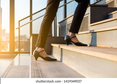Business woman up the stairs. Female legs in high heels shoes walking on the stairs.