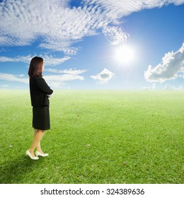Business woman standing to clouds sky in grassland.Vacation and holiday concept.