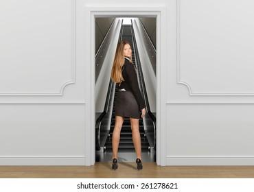 Business woman standing in the doorway going on escalator.