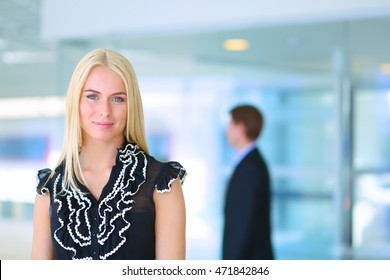 Business woman standing in foreground in office