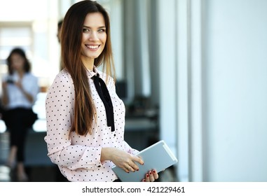 Business woman standing in foreground with a tablet in her hands, her co-workers discussing business matters in the background