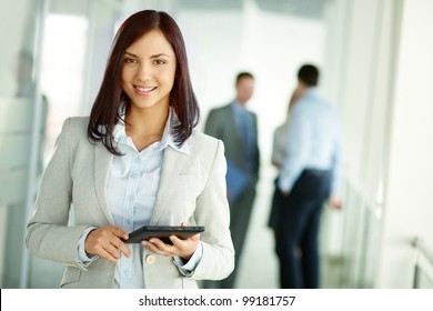 Business woman standing in foreground with a tablet in her hands, her co-workers discussing business matters in the background, tilt up