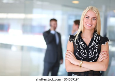 """Business woman standing in foregroundPlease tick the """"R-Rated"""" box when submitting an image of this type."""
