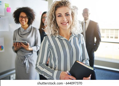 Business woman standing in front of colleagues, mixed races people looking positive