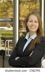 A business woman is standing in front of a glass building looking confident.