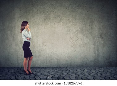business woman standing in front of a wall
