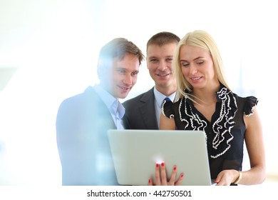 Business woman standing with her staff in background at modern office .