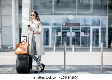 Business woman standing near the airport with luggage during the business trip