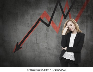 Business woman standing near blackboard with arrows going down. Concept of decline and economical crisis.