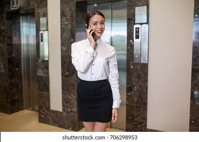 Business woman standing near elevators in business center.