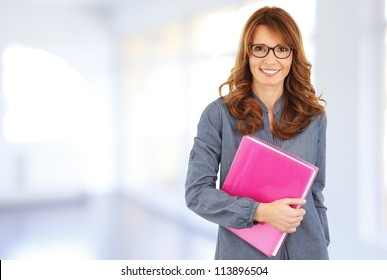 Business woman standing in the office, holding a file in her hands